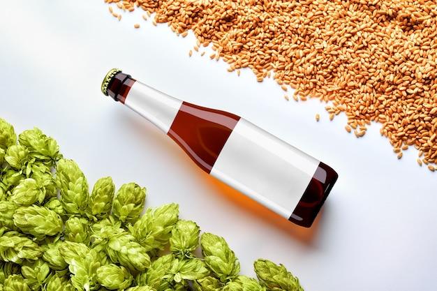 Makieta piwa brązowego z butelką rozmieszczenie po przekątnej na białym tle z pszenicy i chmielu. na szkle znajduje się szara etykieta. szablon gotowy do prezentacji.