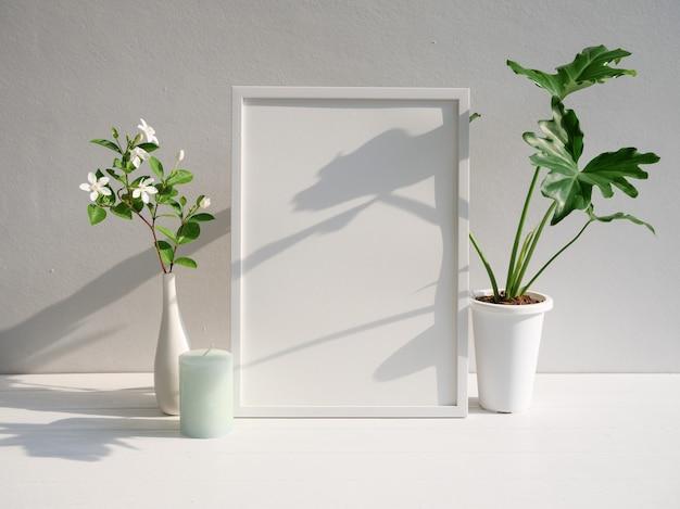 Makieta plakat rama philodendron selloum gardenia kwiat w nowoczesny biały wazon i zielona świeca na białym drewnianym stole i tle ściany cementu z długim cieniem