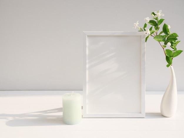 Makieta plakatowa biała ramka i piękny tropikalny kwiatowy kwiat gardenia w nowoczesnym białym wystroju wazonu z zieloną świecą na beżowym stole i cementowej powierzchni ściany z długim cieniem