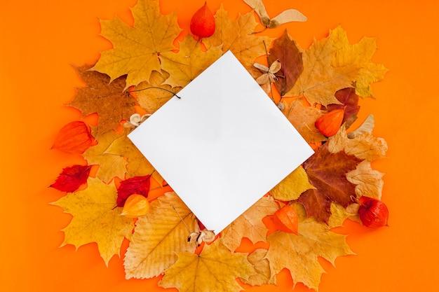 Makieta pocztówki i suche liście na pomarańczowym tle
