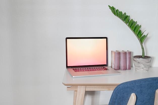 Makieta pracy lub biurka z laptopa, książek i roślin doniczkowych na biały drewniany blat.