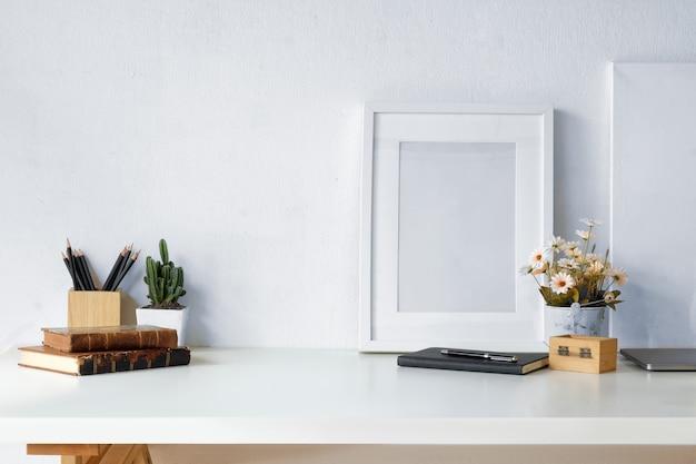 Makieta przestrzeni roboczej rocznika książek, suchych kwiatów, materiały biurowe i ramki plakat