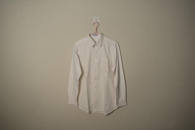 Makieta pusta biała koszula z długimi rękawami na wieszaku na ścianie tło widok z przodu