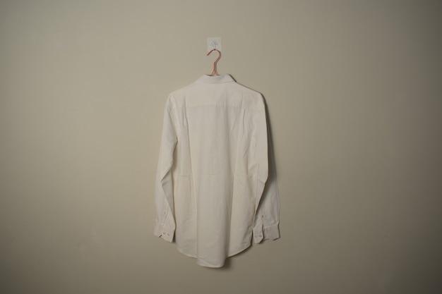 Makieta pusta biała koszula z długimi rękawami na wieszaku na tle ściany widok z tyłu