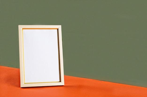 Makieta pusta biała pionowa ramka na zdjęcia. pomarańczowy stół i zielona ściana tło. minimalistyczna koncepcja z miejscem na tekst. makieta z elementami wystroju.