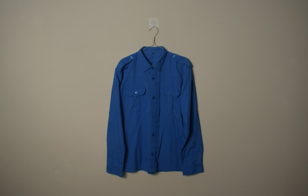 Makieta Pusta Niebieska Koszula Zewnętrzna Z Długim Rękawem Na Wieszaku Na Tle ściany Widok Z Przodu Premium Zdjęcia
