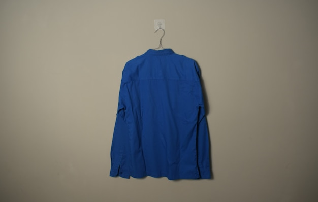 Makieta pusta niebieska koszula zewnętrzna z długim rękawem na wieszaku na tle ściany widok z tyłu