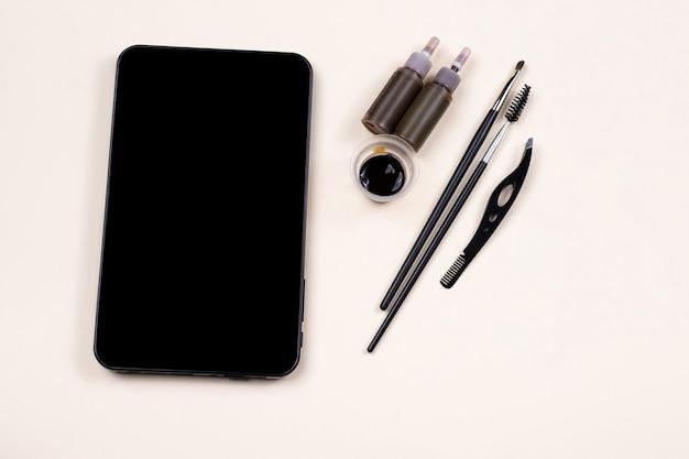 Makieta pustego czarnego ekranu tabletu w pobliżu zestawu do heny brwiowej, procedura pęseta. instrukcja wideo
