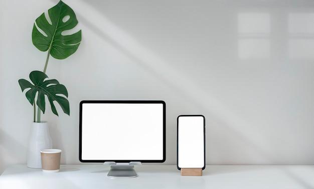 Makieta pustego ekranu tabletu i smartfona na białym stole z miejsca na kopię.