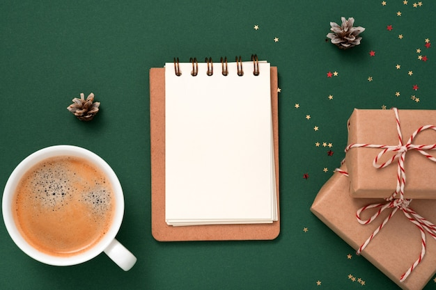 Makieta pustego papieru zeszytu, konfetti złotych gwiazdek, pudełka na prezenty, kubek kawy na zielonym tle