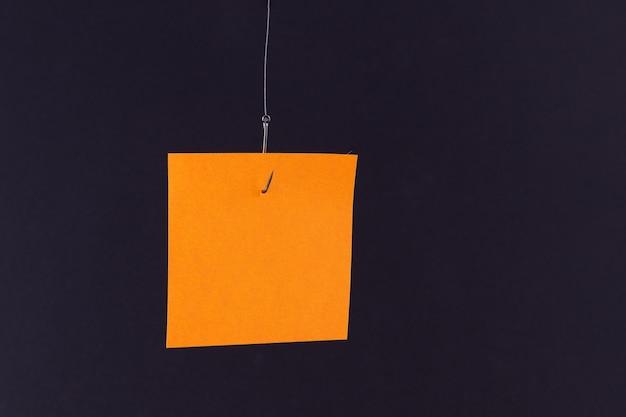 Makieta pustego pomarańczowego papieru notatek z miejscem na kopię wiszącym na haczyku wędkarskim