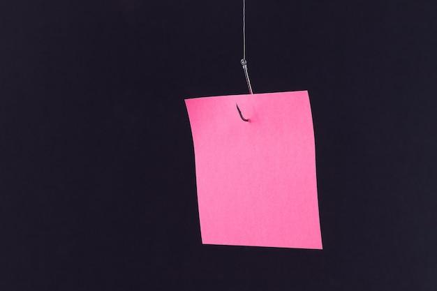 Makieta pustego różowego papieru notatek z miejscem na kopię wiszącym na haczyku wędkarskim