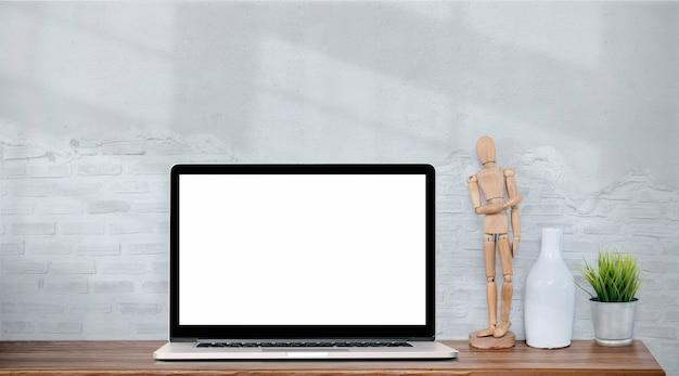 Makieta pusty ekran laptopa na drewnianym stole z białym murem.