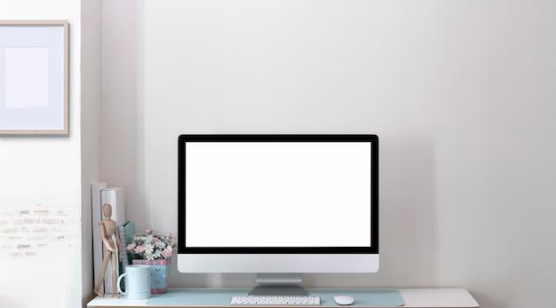 Makieta pusty ekran monitora komputera na drewnianym stole w nowoczesnym pokoju z murem.