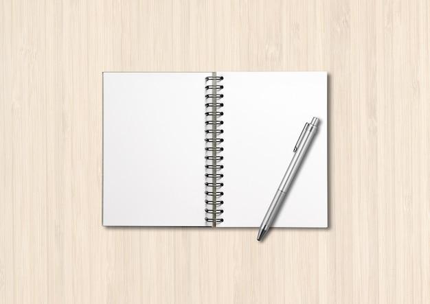 Makieta pusty notatnik otwarta spirala i długopis na białym tle na białe drewno