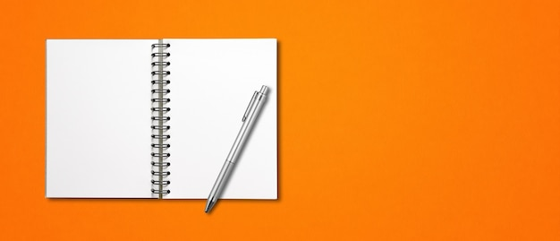 Makieta pusty notatnik otwarta spirala i długopis na białym tle na pomarańczowy poziomy baner