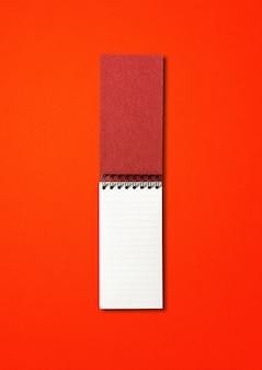 Makieta pusty notatnik otwarta spirala na białym tle na czerwono