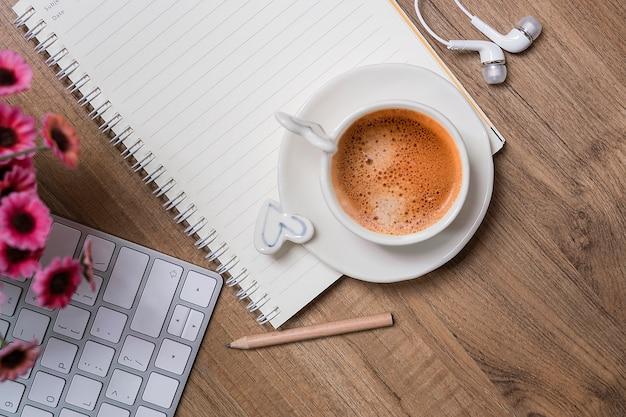 Makieta pusty notatnik z filiżanką kawy i białą komputerową klawiaturą
