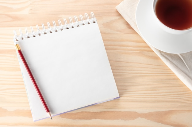 Makieta pusty notatnik z piórem, notatnikiem i filiżanką herbaty na drewnianym stole.