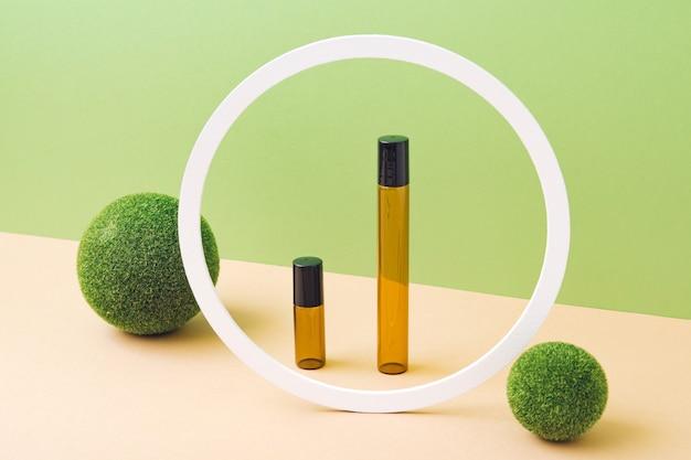 Makieta pustych butelek na kosmetyki wykonana z ciemnego szkła na jasnobrązowym i zielonym tle. zabieg na ciało i twarz oraz spa. naturalne kosmetyki. olejek do masażu. skopiuj miejsce.