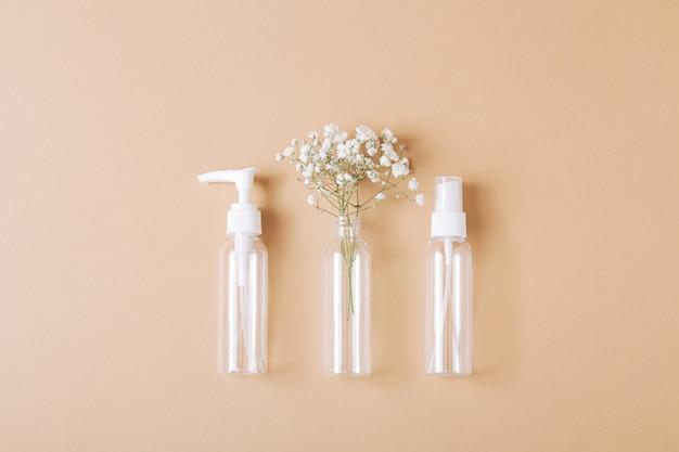 Makieta pustych butelek na kosmetyki wykonana z przezroczystego szkła na jasnobrązowym tle. zabieg na ciało i twarz oraz spa. naturalne kosmetyki. olejek do masażu. skopiuj miejsce.