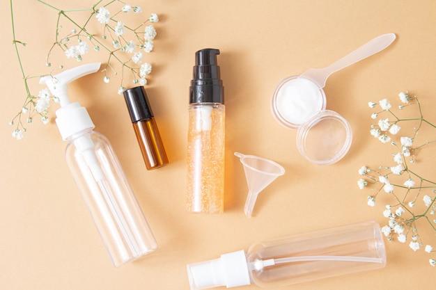 Makieta pustych butelek po kosmetykach wykonana z ciemnego i przezroczystego szkła na jasnobrązowym tle. zabieg na ciało i twarz oraz spa. naturalne kosmetyki. olejek do masażu. skopiuj miejsce. płaskie ułożenie