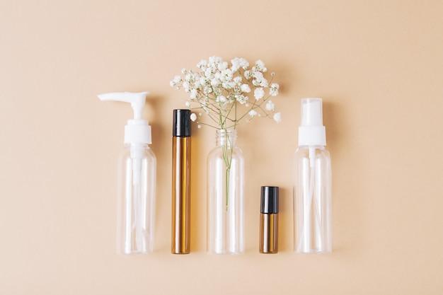 Makieta pustych butelek po kosmetykach wykonana z ciemnego i przezroczystego szkła na jasnobrązowym tle. zabieg na ciało i twarz oraz spa. naturalne kosmetyki. olejek do masażu. skopiuj miejsce