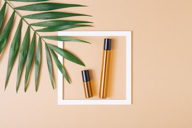 Makieta pustych butelek po kosmetykach wykonana z ciemnego szkła z liściem palmowym i białą ramką. zabieg na ciało i twarz oraz spa. naturalne kosmetyki. antycellulitowy olejek do masażu. skopiuj miejsce