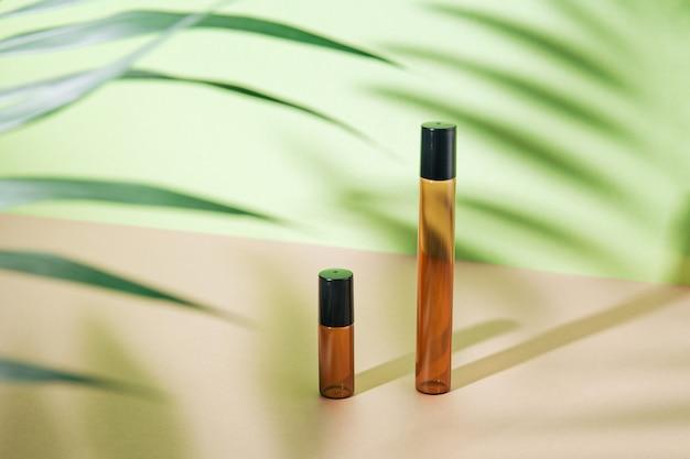 Makieta pustych butelek po kosmetykach wykonana z ciemnego szkła z liściem palmowym i twardym cieniem. zabieg na ciało i twarz oraz spa. naturalne kosmetyki. antycellulitowy olejek do masażu. skopiuj miejsce