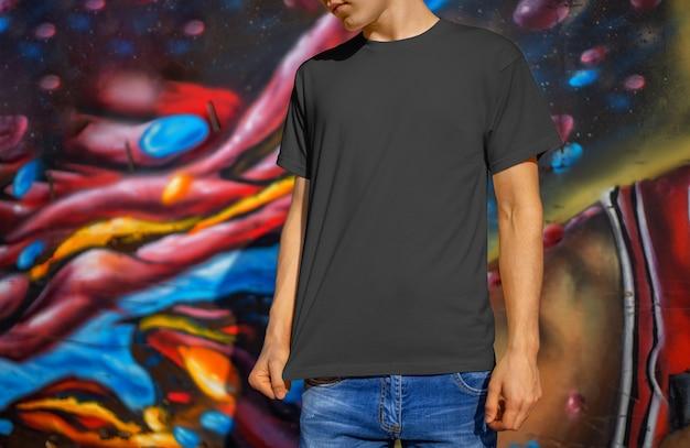 Makieta pustych ubrań na młodego faceta w dżinsach na tle ściany z graffiti. szablon czarnej koszulki do prezentacji wzoru i wzoru oraz reklamy w sklepie internetowym