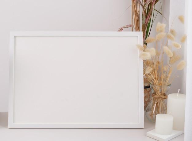 Makieta rama plakatu suszona kompozycja kwiatów lagurus ovatus w nowoczesnym szklanym wazonie i świece na białym stole i tle ściany cementu