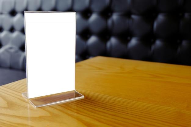 Makieta ramka menu stoi na drewnianym stole w kawiarni barowej. miejsca na tekst