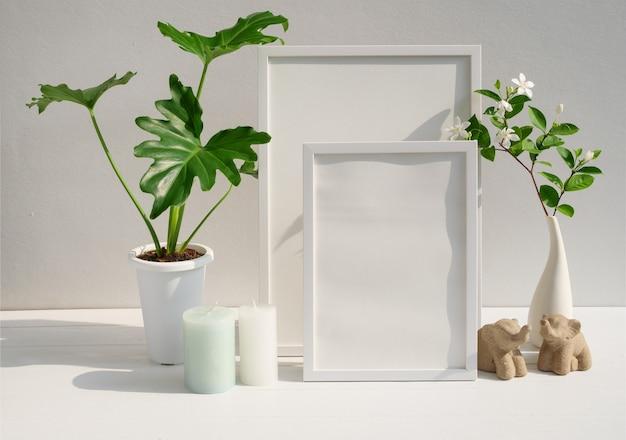 Makieta ramka na plakat roślina philodendron kwiat gardenia w nowoczesnym białym wazonie świeca i słonie stoją na stole spa i cementowej powierzchni ściany z długim cieniem