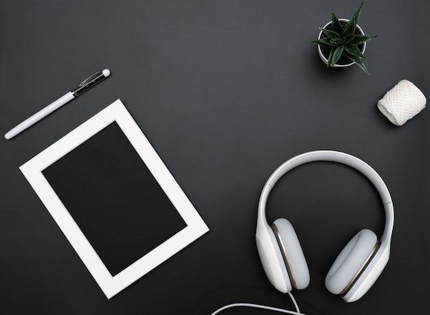 Makieta, ramka na zdjęcia, słuchawki, długopis i kaktus napisz obiekt na czarnym tle