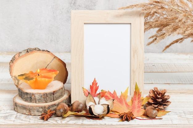 Makieta ramka na zdjęcia z dekoracjami z jesiennych liści i płonącą świecą na drewnianym stojaku
