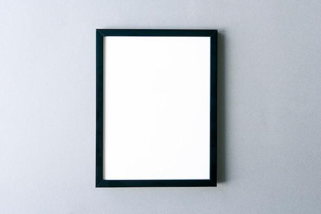 Makieta ramki, czarna ramka na zdjęcia z pustą powierzchnią na szarej ścianie. miejsce na tekst.