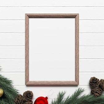 Makieta ramki na białej drewnianej podłodze z świątecznych dekoracji