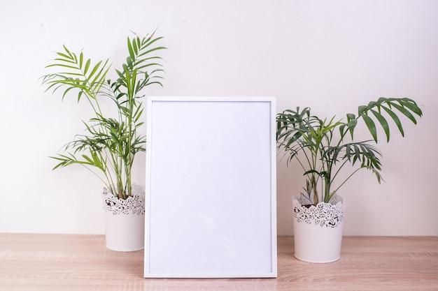 Makieta ramki na zdjęcia portretowe biały na drewnianym stole. nowoczesny wazon ceramiczny. tło białe ściany. skandynawskie wnętrze.