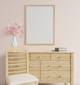 Makieta ramki na zdjęcia różowej ściany z różowym wazonem z kwiatami i pustymi książkami na stole i krzesłem z przodu. renderowanie 3d.