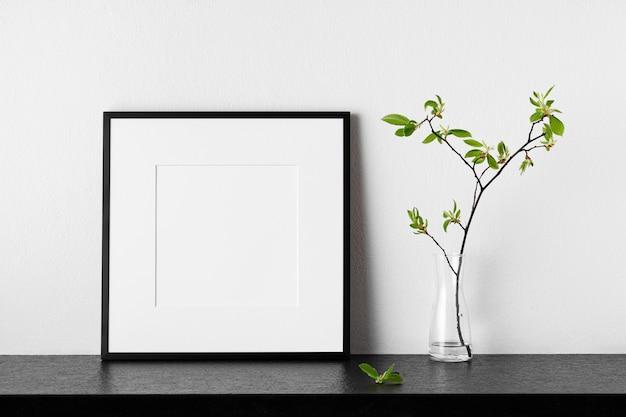 Makieta ramki. plakat z rośliną w wazonie. czarna kwadratowa ramka na zdjęcia z passepartout. widok z boku. może służyć jako szablon do projektów i dzieł sztuki.