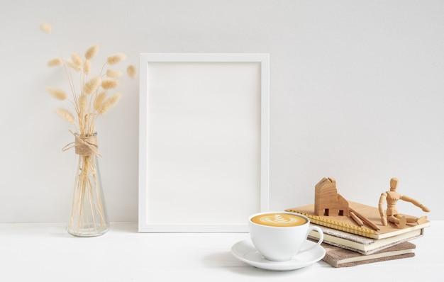 Makieta ramki plakatowej, filiżanka kawy, książka rzemieślnicza, model domu i suszone kwiaty lagurus ovatus