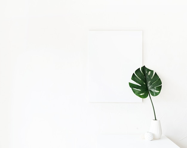 Makieta ramki plakatowej na stoliku do kawy z dekoracjami na tle białej ściany