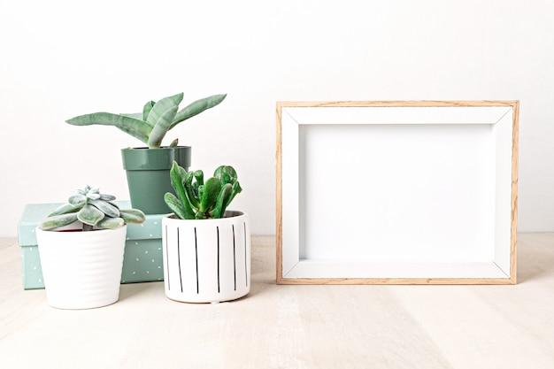 Makieta ramki plakatowej, widok z przodu, z elementami dekoracyjnymi, roślinami domowymi, kwiatami i pustym miejscem na kopię nad białą ścianą. miejsce na tekst lub zdjęcie