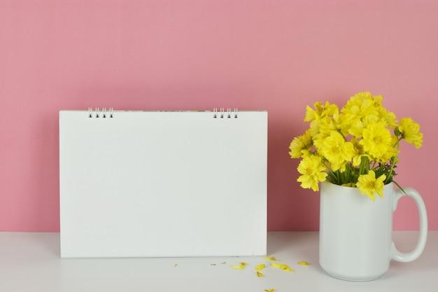 Makieta ramki pusty kalendarz z żółtymi kwiatami w wazonie na różowo