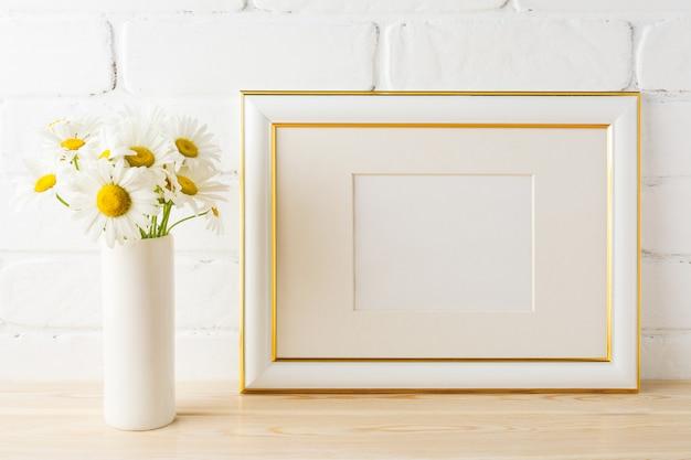 Makieta ramki zdobione złotym krajobrazem z kwiatem stokrotki w wazonie