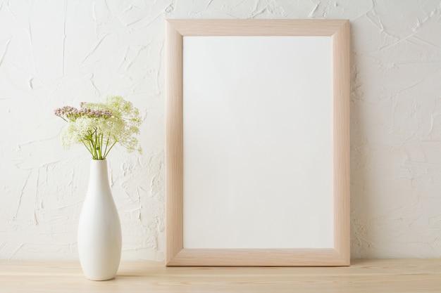 Makieta ramowa z delikatnymi kwiatami w białym stylowym wazonie
