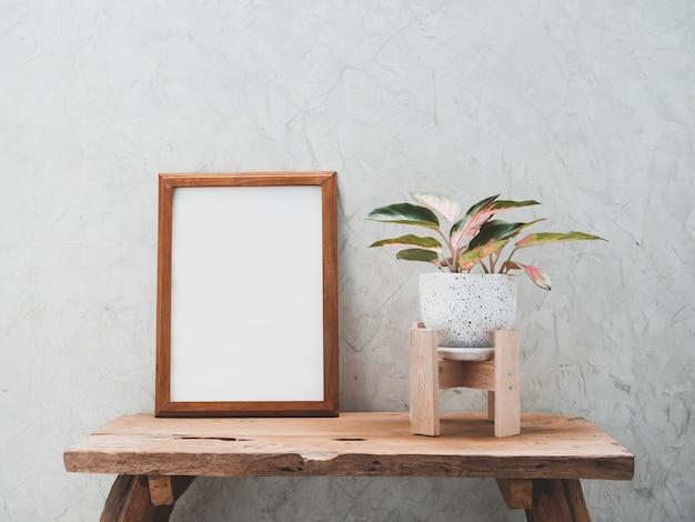Makieta ramy z drewna tekowego i rośliny doniczkowej aglaonema w nowoczesnym biało-czarnym ceramicznym pojemniku