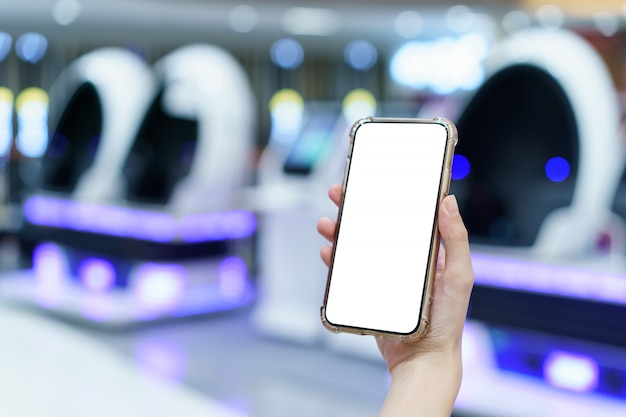 Makieta, ręce trzymając pusty biały ekran telefon komórkowy w niewyraźnym centrum gry