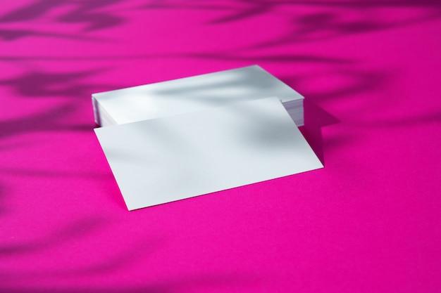 Makieta reklamowa. białe puste wizytówki na jasnym różowym tle