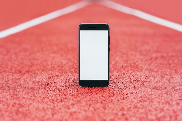 Makieta smartfona na stadionie do biegania.